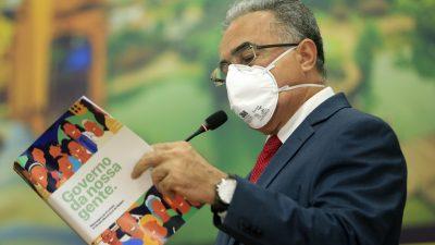 Edmilson usa máscara enquanto discursa. Ele segura um livro, da prefeitura, onde se lê: Governo da nossa gente