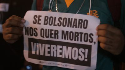 """pessoa segura um cartaz, onde se lê: """"Se Bolsonaro nos quer mortos, VIVEREMOS!"""""""