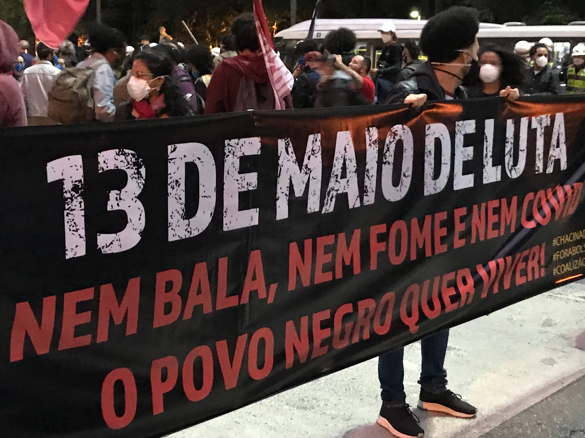 Pessoas seguram uma faixa, onde se lê: 13 de maio de luta. Nem bala, nem fome e nem covid. O povo negro quer viver.