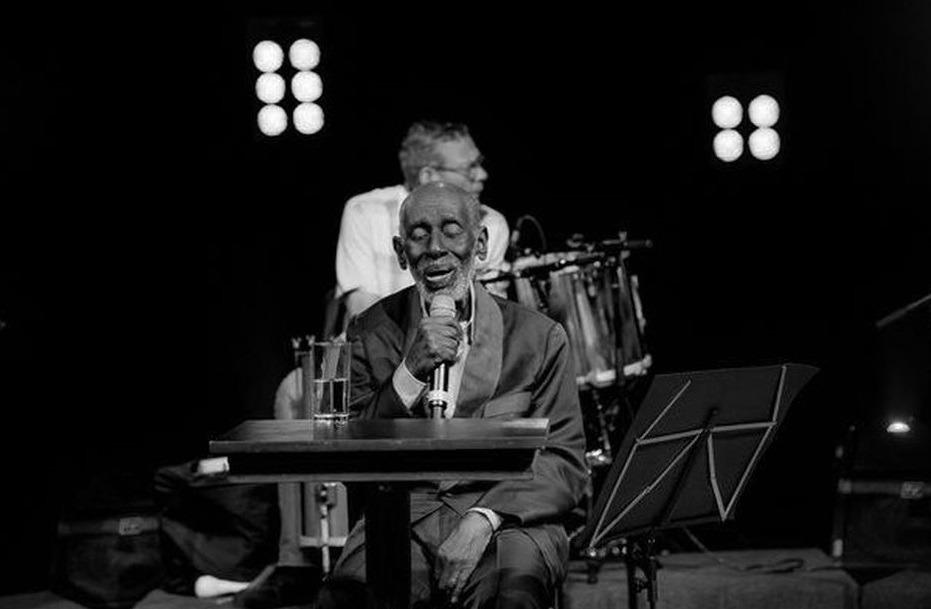 Nelson Sargento está sentado à mesa, no palco, cantando segurando o microfone. Ao fundo, um músico. A foto é preto e branco e há luzes dos dois lados