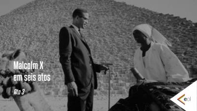 Malcolm em seis atos - Ato 3. Foto mostra ele conversando com uma mulher negra, tendo ao fundo uma pirâmide