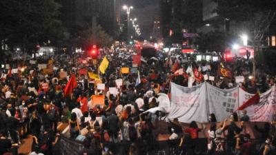 Foto mostra a Av. Paulista, à noite, tomada por manifestantes, de costas, caminhando.