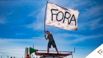 Homem segura ao alto uma bandeira branca onde se lê a palavra FORA.Ele está em cima de um carro. ao fundo, o céu azul de Brasília.