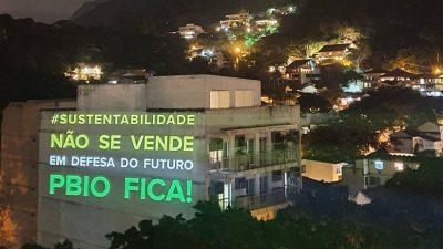 Em um prédio, estão projetados as frases: Sustentabilidade não se vende. Em defesa do futuro PNBIO FICA!