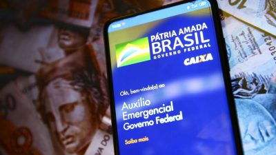 celular com tela do aplicativo do auxilio emergencial e a logomarca do governo federal. Ao fundo, notas de dinheiro