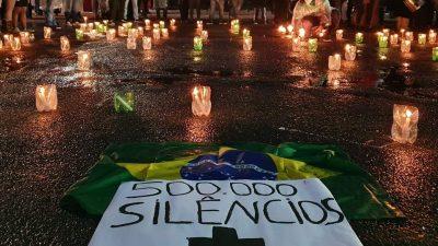 Foto mostra velas acesas e um cartaz no chão, escrito 500.000 silêncios. com uma cruz e uma bandeira do Brasil