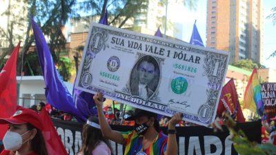 Manifestante carrega reprodução de nota de um dólar com a foto de Bolsonaro, e na nota, a frase? Sua vida vale 1 dólar?. Ela usa uma bandeira LGBT pendurada, como um lenço e a camisa do MST. A seu redor, faixas e bandeiras.