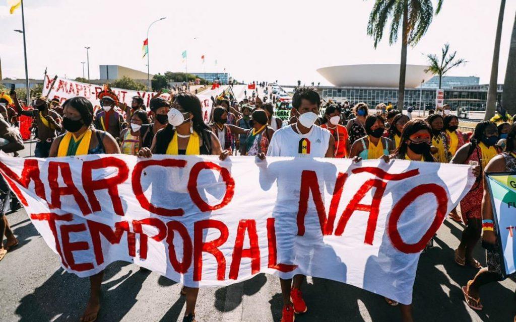 Protesto de indígenas em Brasília. Eles carregam uma faixa, onde se lê Marco Temporal Não.