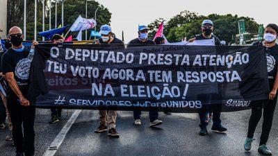 """Trabalhadores seguram faixa, com a frase: """"O deputado, presta atenção. Teu voto agora tem resposta na eleição!"""
