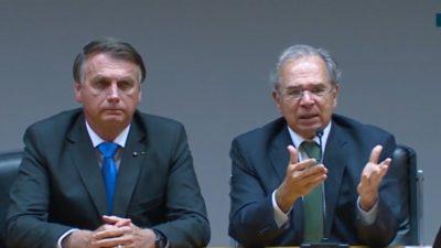 Bolsonaro está à esquerda, de terno escuro e gravata azul. Guedes, ao seu lado, está falando, com gravata cinza e com as mãos para a frente.