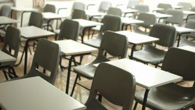 foto mostra várias cadeiras escolares vazias