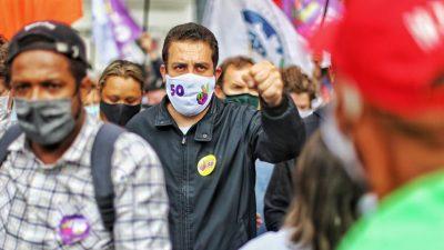 Guilherme boulos em campanha. Ele usa camisa azul escuro de mangas compridas, máscara branca, com o número 50. Está com a mão esquerda para a frente,com o punho fechado. Ao seu lado, Orlando (PCdoB)
